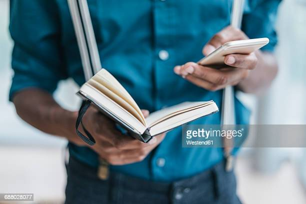 Young man using smart phone, holding note book
