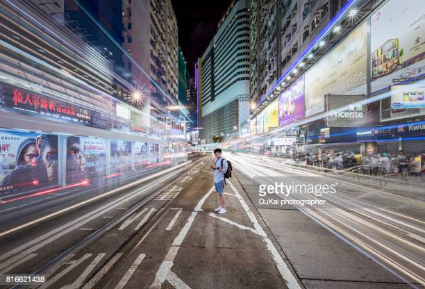 young man using smart phone in city street at night - long exposure stock pictures, royalty-free photos & images