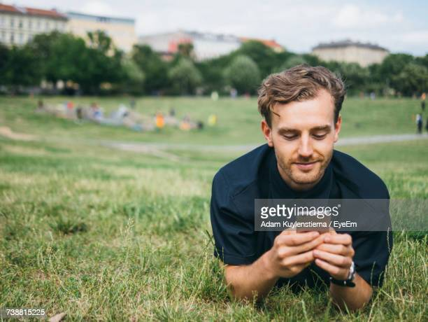 young man using smart phone in park - gras stock pictures, royalty-free photos & images