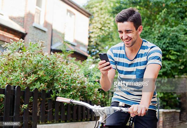 young man using smart phone on bike - one young man only stock pictures, royalty-free photos & images