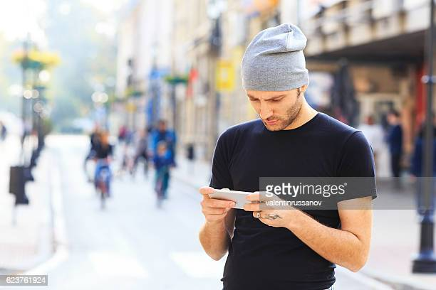 Young man using smart phone on street