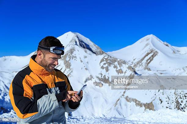 Young man using smart phone on top snow mountain