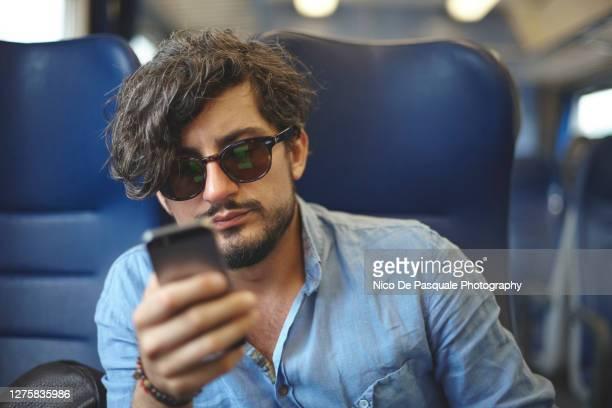 young man using smart phone - bahnreisender stock-fotos und bilder