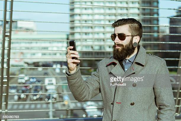 young man (hipster style) using smart phone - pjphoto69 stock pictures, royalty-free photos & images