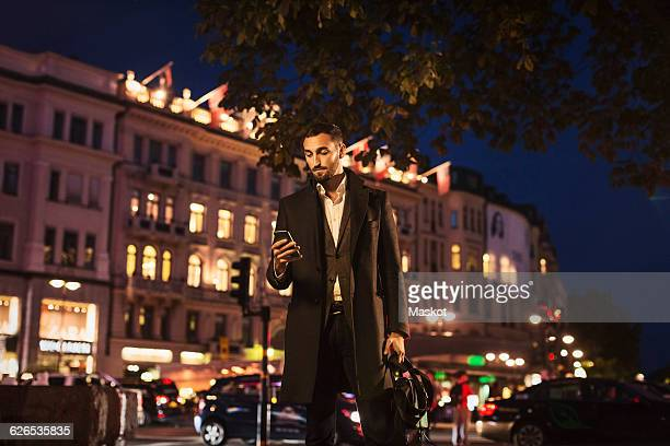 young man using smart phone while standing on city street at night - long coat stock pictures, royalty-free photos & images