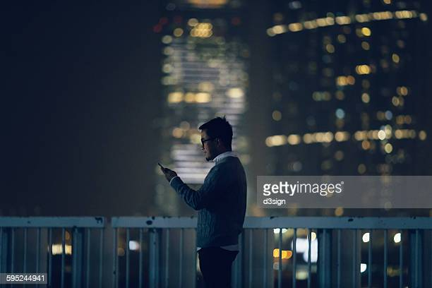 Young man using smartphone in city street at night