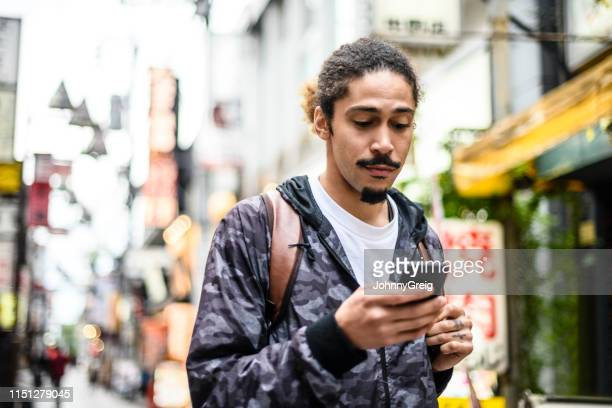young man using smartphone in city street - goatee stock pictures, royalty-free photos & images