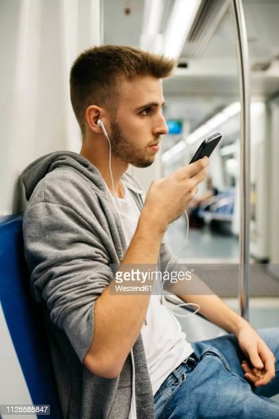 young man using smartphone in metro - 18 19 anos imagens e fotografias de stock