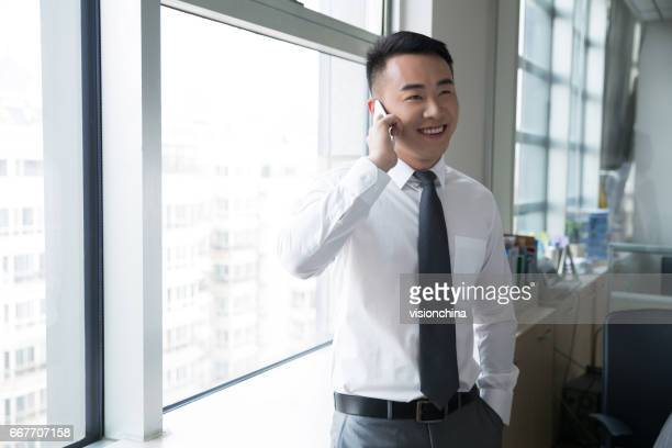 young man using smartphone near by window