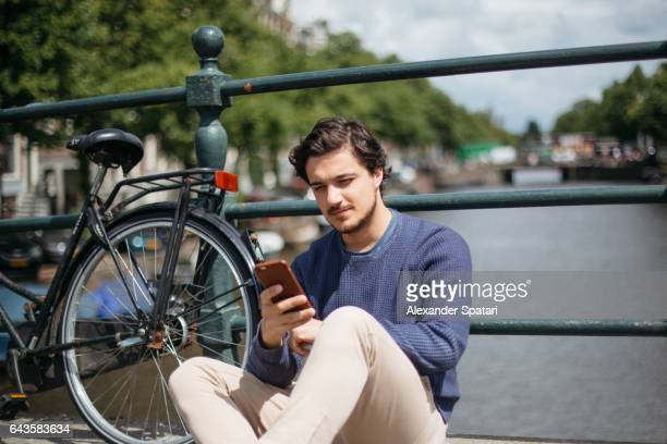 Young man using smartphone near the canal in Amsterdam leaning to a bike