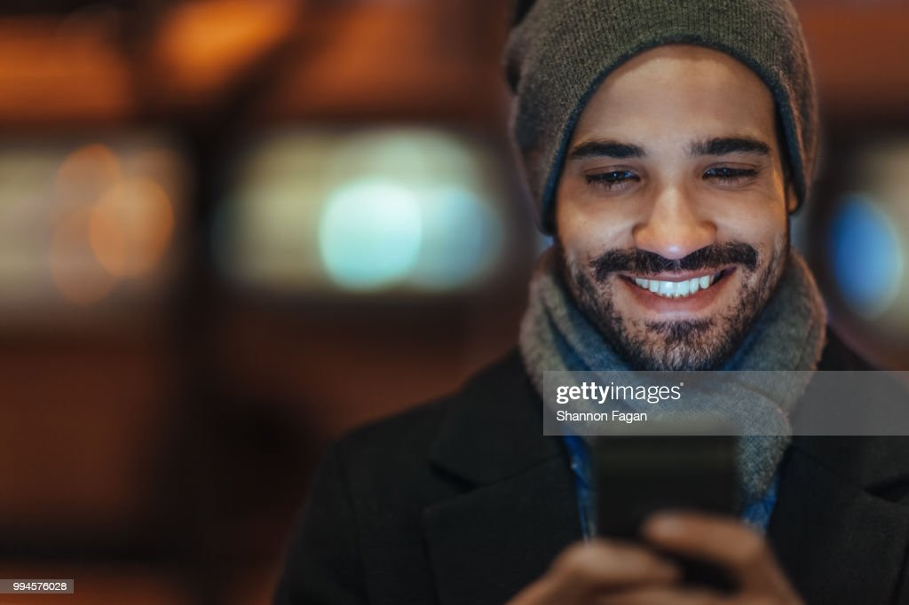 Young man using smartphone on city street at night : Stock Photo