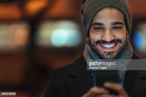 young man using smartphone on city street at night - stralende lach stockfoto's en -beelden