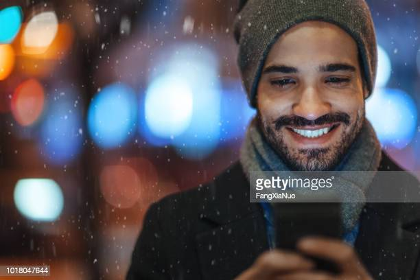 young man using smartphone on city street on a snowy day - mobile app stock pictures, royalty-free photos & images