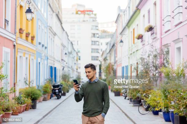 Young man using smartphone on the multi colored street in Paris, France