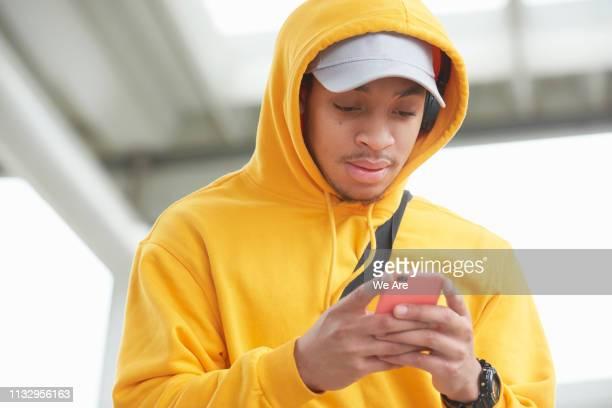 young man using smartphone - capuchon stockfoto's en -beelden
