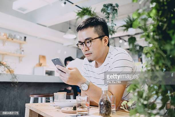 Young man using smartphone relaxingly in a cafe