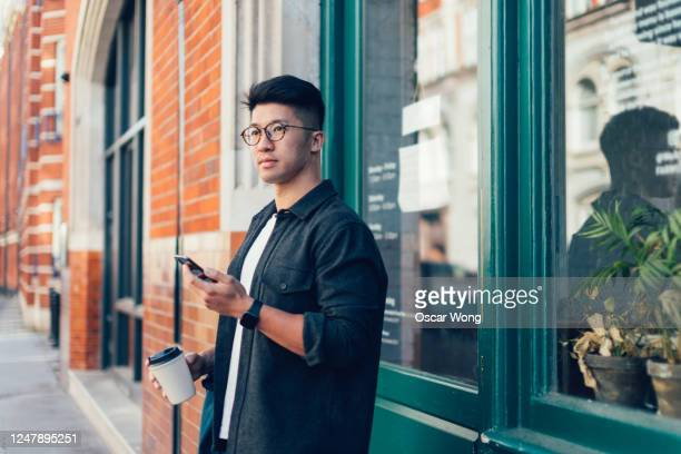 young man using smartphone while having coffee outside a cafe - leisure activity stock pictures, royalty-free photos & images