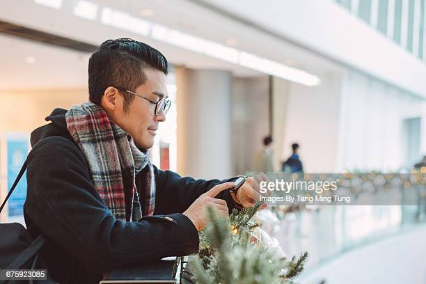 young man using smartwatch in mall. - half shaved hairstyle stock pictures, royalty-free photos & images