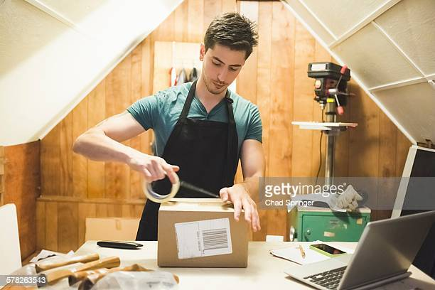Young man using sticking tape to prepare package for delivery