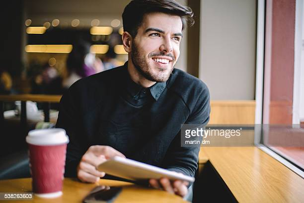 Young man using tablet in cafe