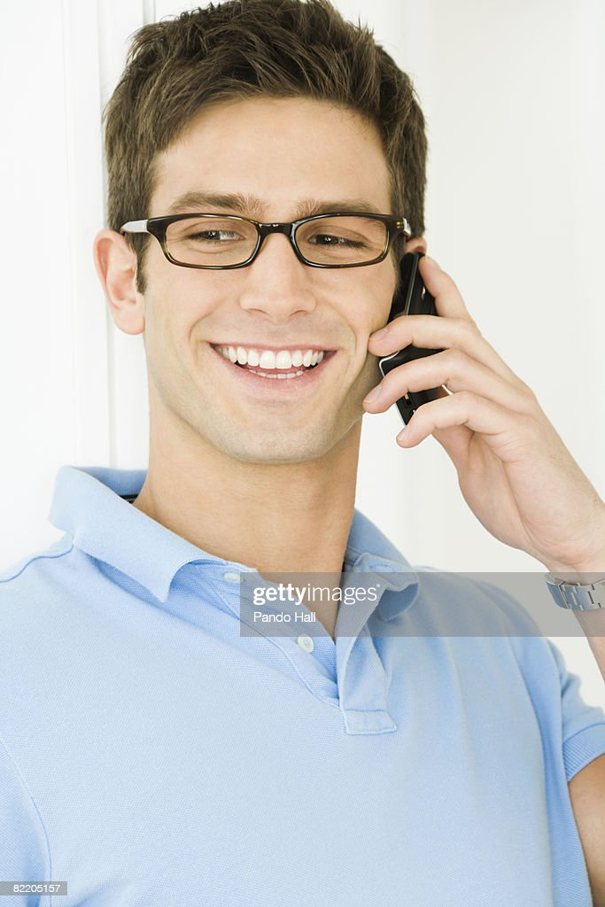 Young man using telephone, smiling : Stock Photo