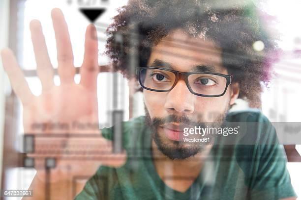 Young man using transparent touchscreen display