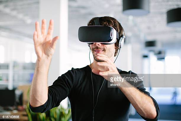 young man using virtual reality glasses - virtual reality simulator stock photos and pictures