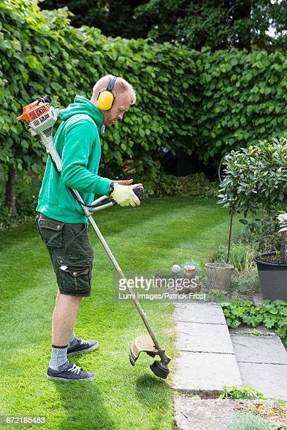 Young man using weed trimmer