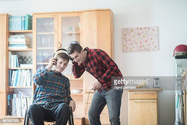 young man using wheelchair listening to headphone music with friend in kitchen - sigrid gombert stock pictures, royalty-free photos & images