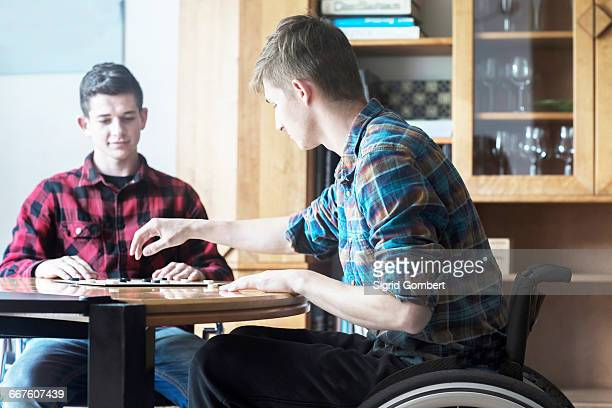 young man using wheelchair playing draughts with friend in kitchen - sigrid gombert stock pictures, royalty-free photos & images