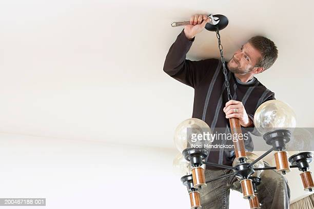 Young man using wrench to hang lighting fixture from ceiling