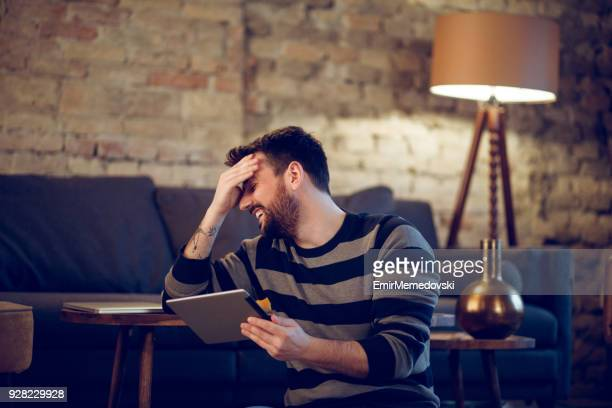 young man video chatting on digital tablet indoors - webcam stock photos and pictures
