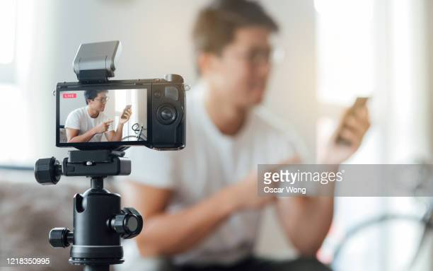 young man vlogging technology product at home - 三脚 ストックフォトと画像