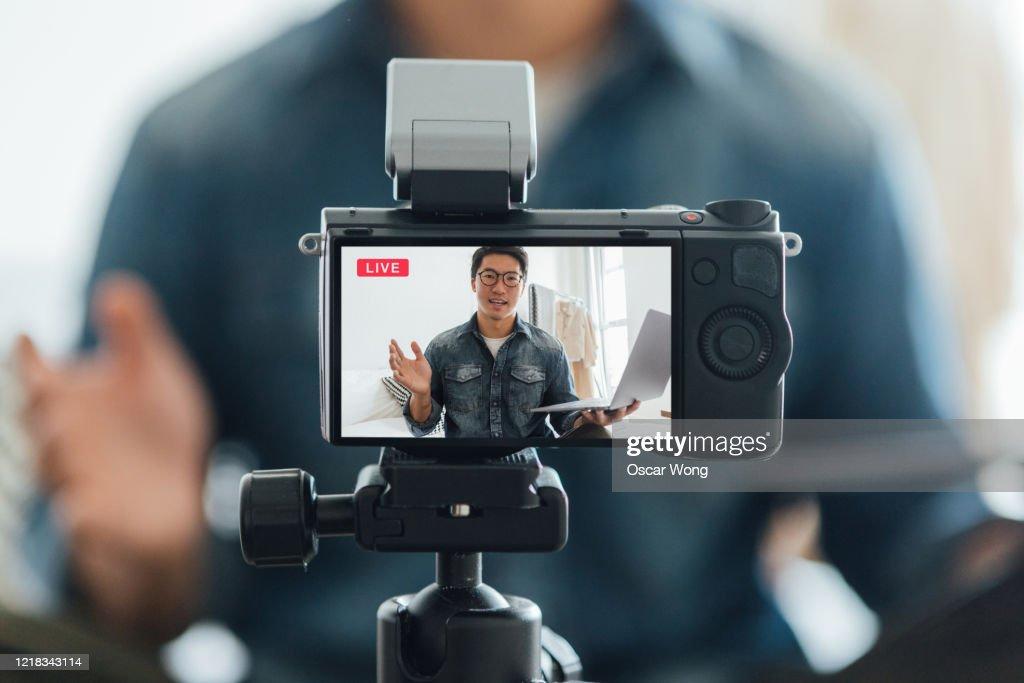 Young Man Vlogging Through Video Camera At Home : Stock Photo