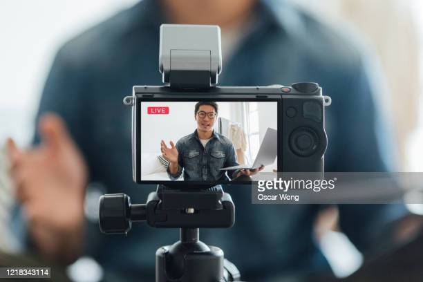 young man vlogging through video camera at home - the media stock pictures, royalty-free photos & images
