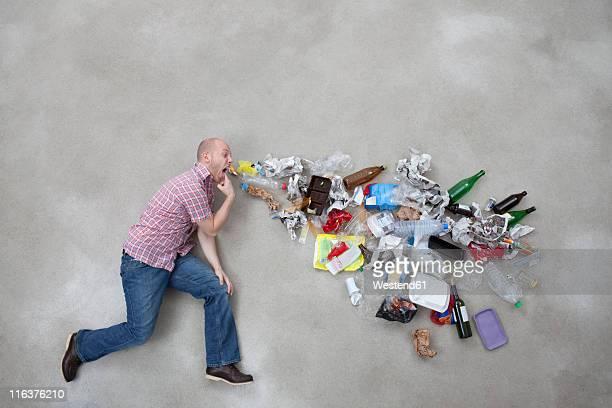Young man vomiting garbage