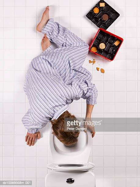 Young man vomiting into toilet bowl, directly above