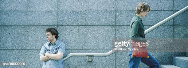 young man waiting as passer-by goes up stairs - moving past stock photos and pictures