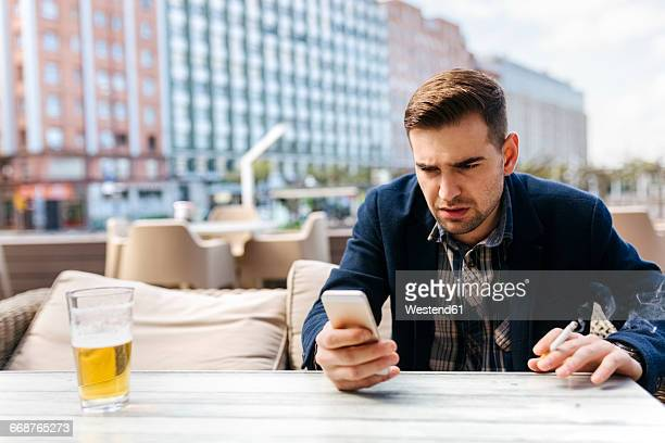 young man waiting at outdoor cafe looking at cell phone - ongeduldig stockfoto's en -beelden