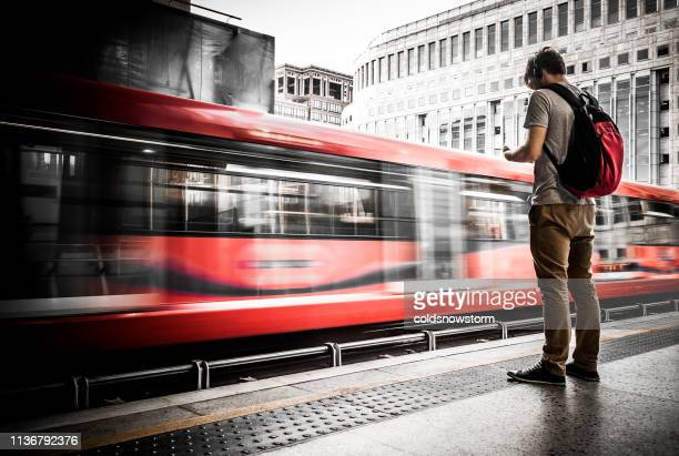 young man waiting at train station with speeding train motion blur - red stock pictures, royalty-free photos & images