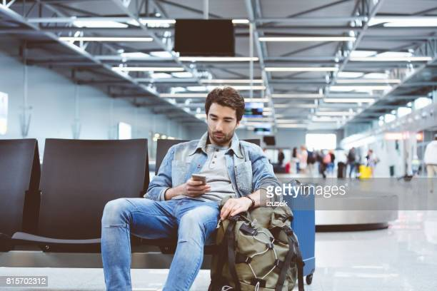 Young man waiting for flight at airport lounge