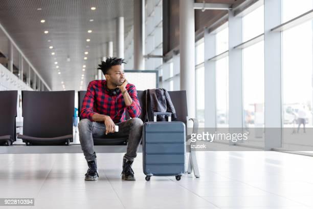 jovem esperando para o voo no saguão do aeroporto - izusek - fotografias e filmes do acervo