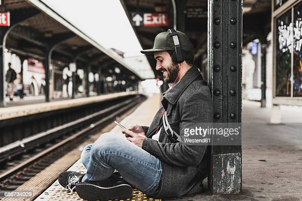 young man waiting for metro at train station platform, using smart phone - subway station stock pictures, royalty-free photos & images