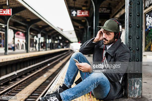 Young man waiting for metro at train station platform, using smart phone