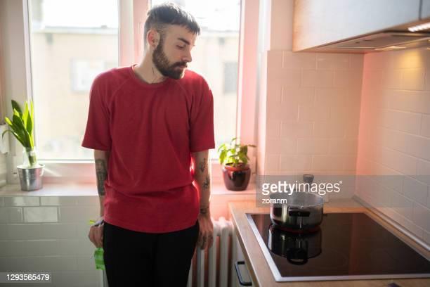 giovane in attesa che l'acqua nella padella bolle - solo un uomo foto e immagini stock