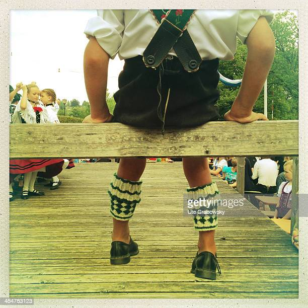 A young man waiting his turn sitting on a railing next to the wooden dance floor and wearing Bavarian national costume featuring woolen half...