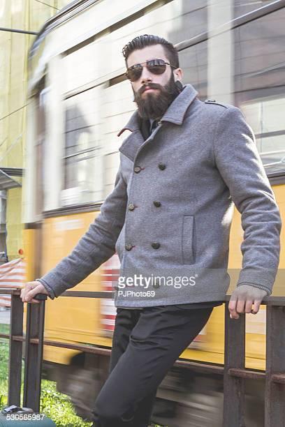 giovane uomo elegante hipster di attesa per () vicino linea tranviaria - pjphoto69 foto e immagini stock
