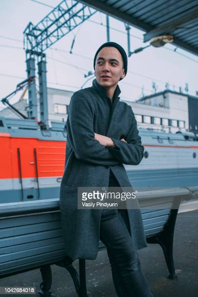 Young man waiting on railroad station platform