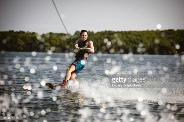 young man wakeboarding, lake simcoe, ontario, canada - waterskiing stock photos and pictures
