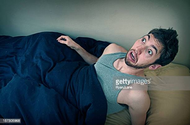 young man wakes up from bad dream - waking up stock pictures, royalty-free photos & images